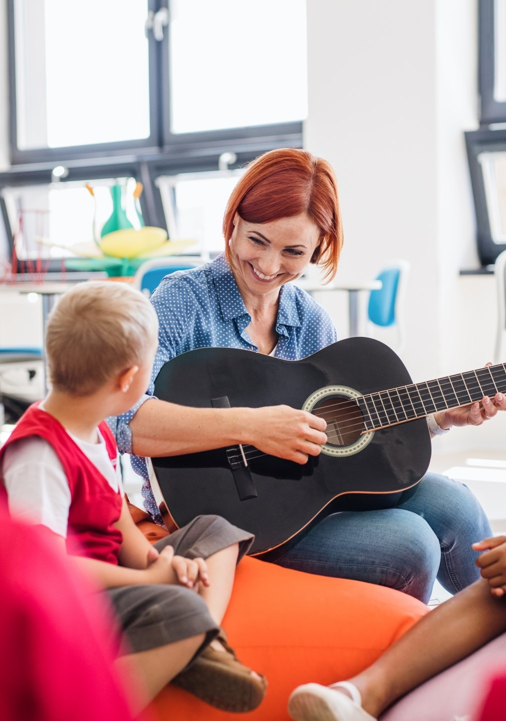 Image of woman playing the guitar to a kid